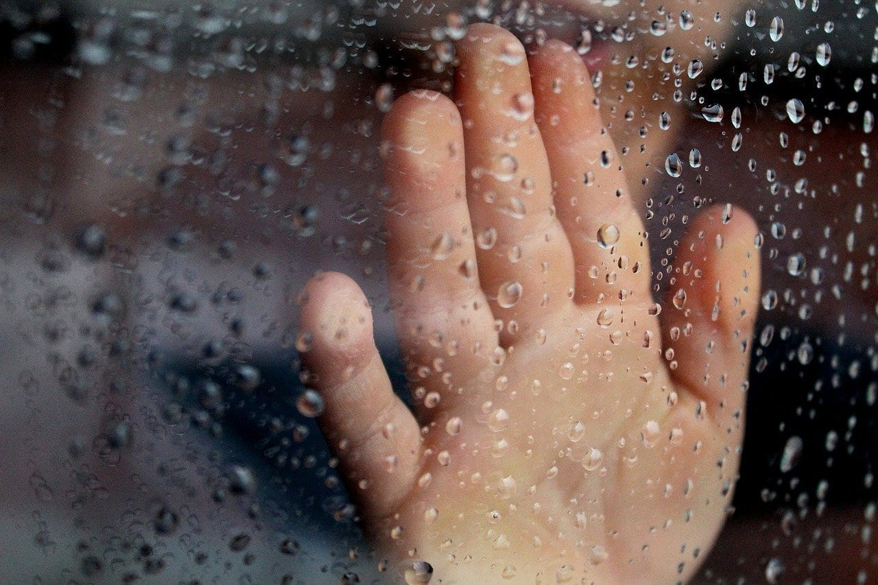 Person touching Glass Window With Rain Droplets